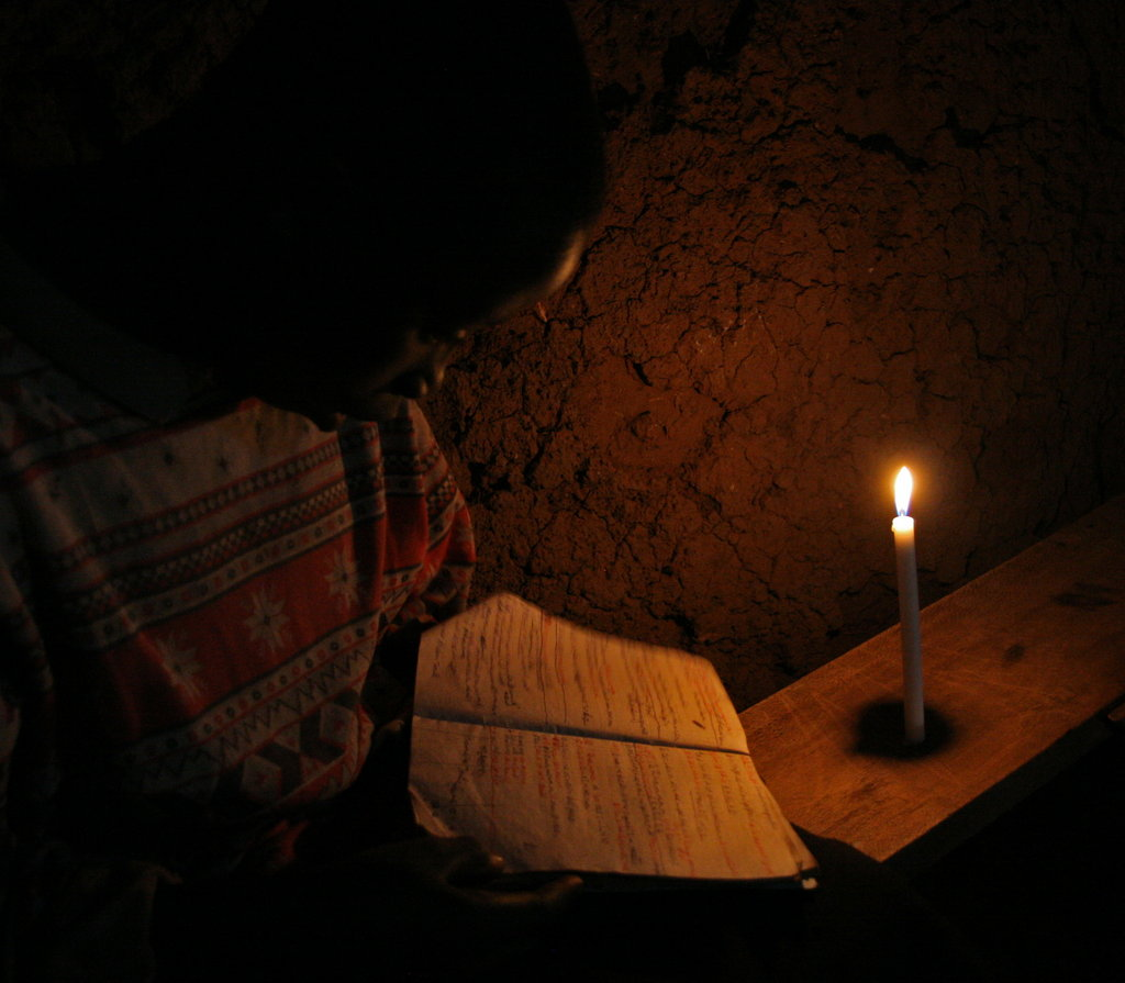 The dangers of the flame - risking fire & eyes to study  (Rwandan girl studying to a weak flame)