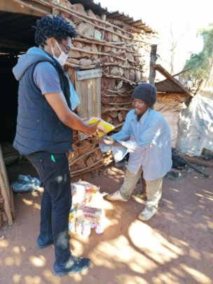 Thabo (one of our outreach nurses) hands over food