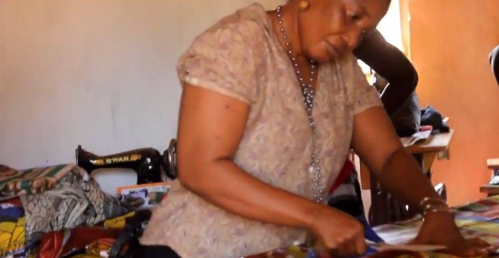 Mariama cuts fabric for dress