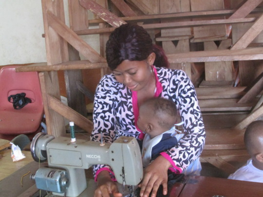 Trainee sewing with child in hand
