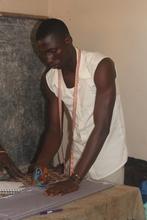 Tailoring trainee sews uniform