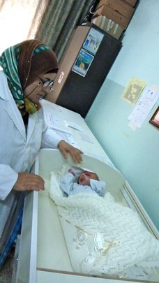 Staff and tiny patient at the clinic in Tayaseer