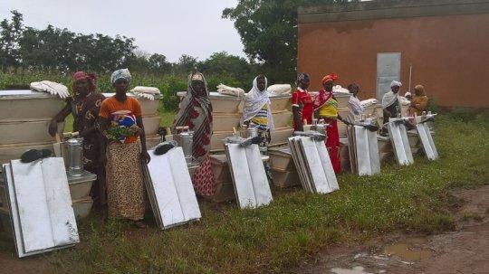 Women in front of their beekeeping equipment