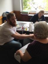 A new Time Bank member enjoys a hand massage