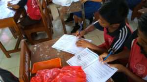 SDN 1 Lembongan students and their workbooks