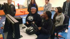 Teens practice driving on the simulator.