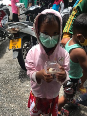 Child receiving food aid from Tamar Center