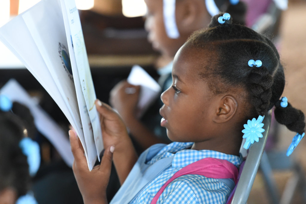 A student reads a mother tongue book at school.