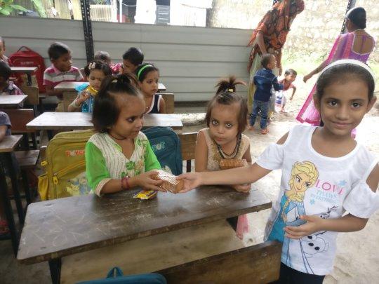 Ananya & Ritika distributing sweets to tiny-tots