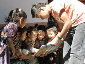 Juan Carlos reading to children in his community
