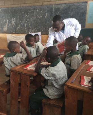 Teacher Jean d'Amour w/ P2 class at Kibara primary