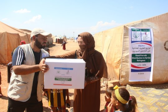 A Syrian widow receiving relief goods