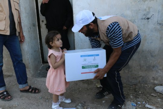 An orphan receiving relief packet.