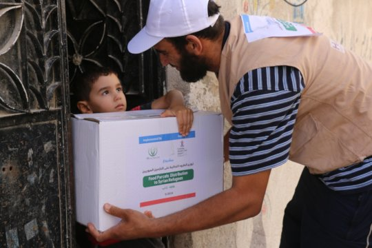 Syrian child receiving relief goods.