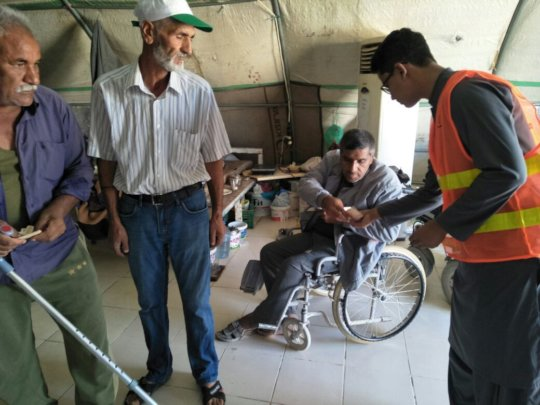 Handing over cash to the disabled Syrian Refugees