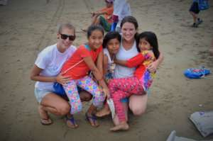 Volunteers with youth during beach clean up
