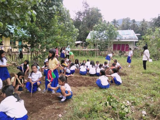 Girls working with their teachers to prep garden