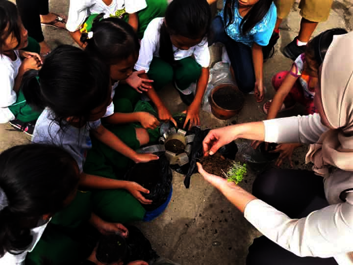 Teacher showing students how to plant in pots