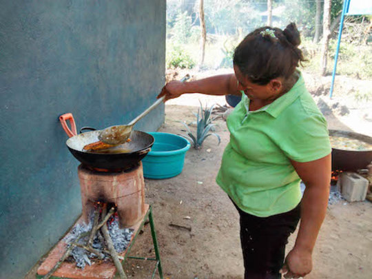 A mother cooking using an ecostove.
