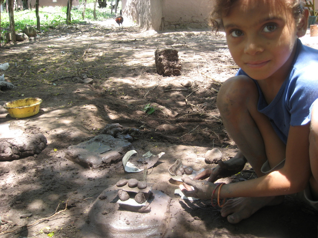 A young girl builds a model stove, like her mother.
