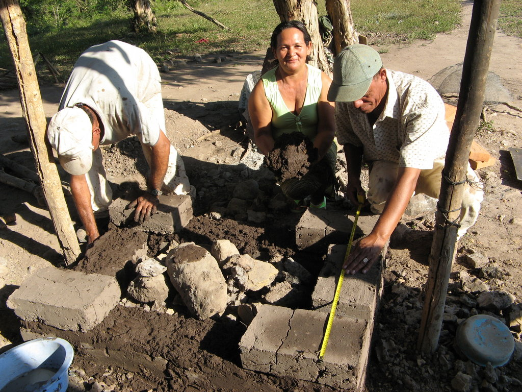 A proud mother in Guatemala helping build her own stove.