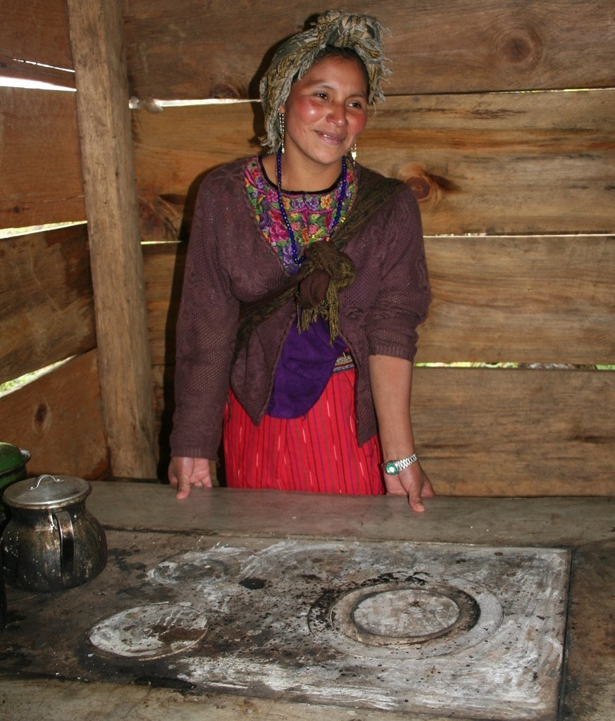 A young mother in Guatemala smiling proudly over her new stove that she helped construct.
