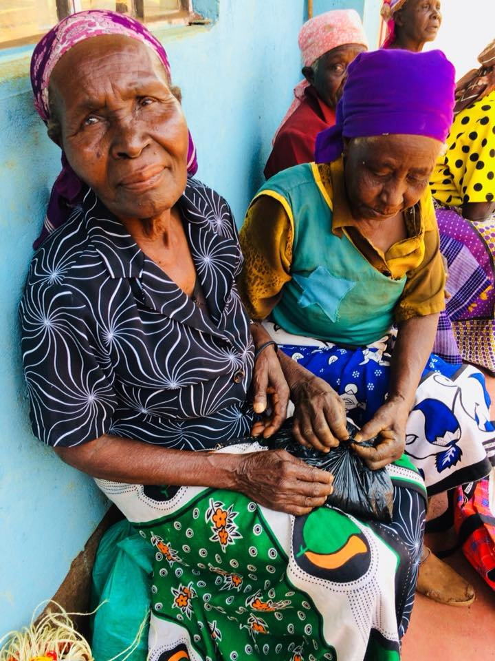 Grandmothers receiving donation of beans and maize