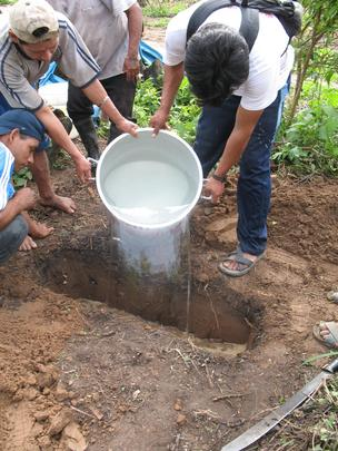Villagers conducting ground percolation test for greywater drain