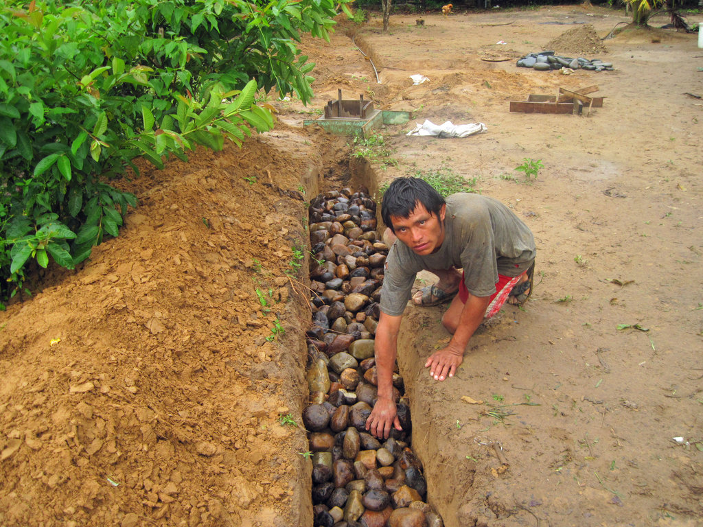 Water committee member building a greywater drain.
