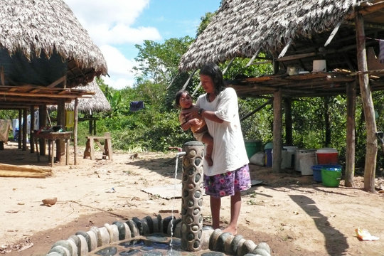 Matsigenka mother bathing her baby at her tap.