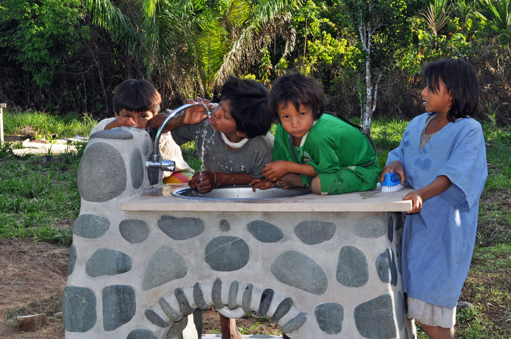 Children drinking clean H2O from school sink.