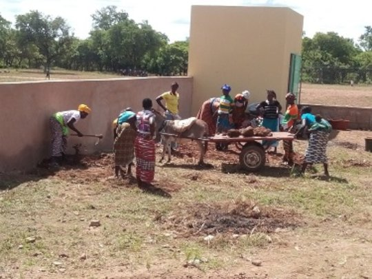 Mothers cleaning the yard of the new school