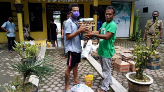 Darma distributing food parcels in Bukit Lawang