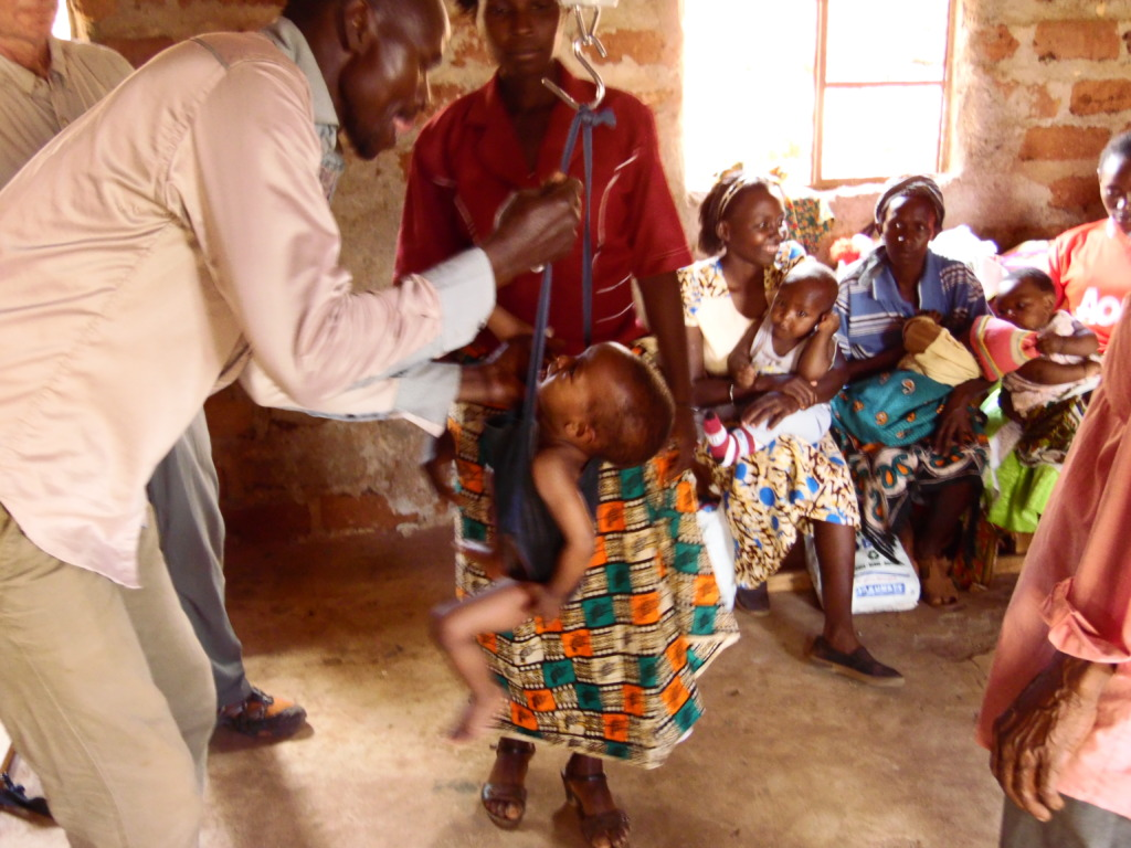 CHW weighing a child during outreach clinic