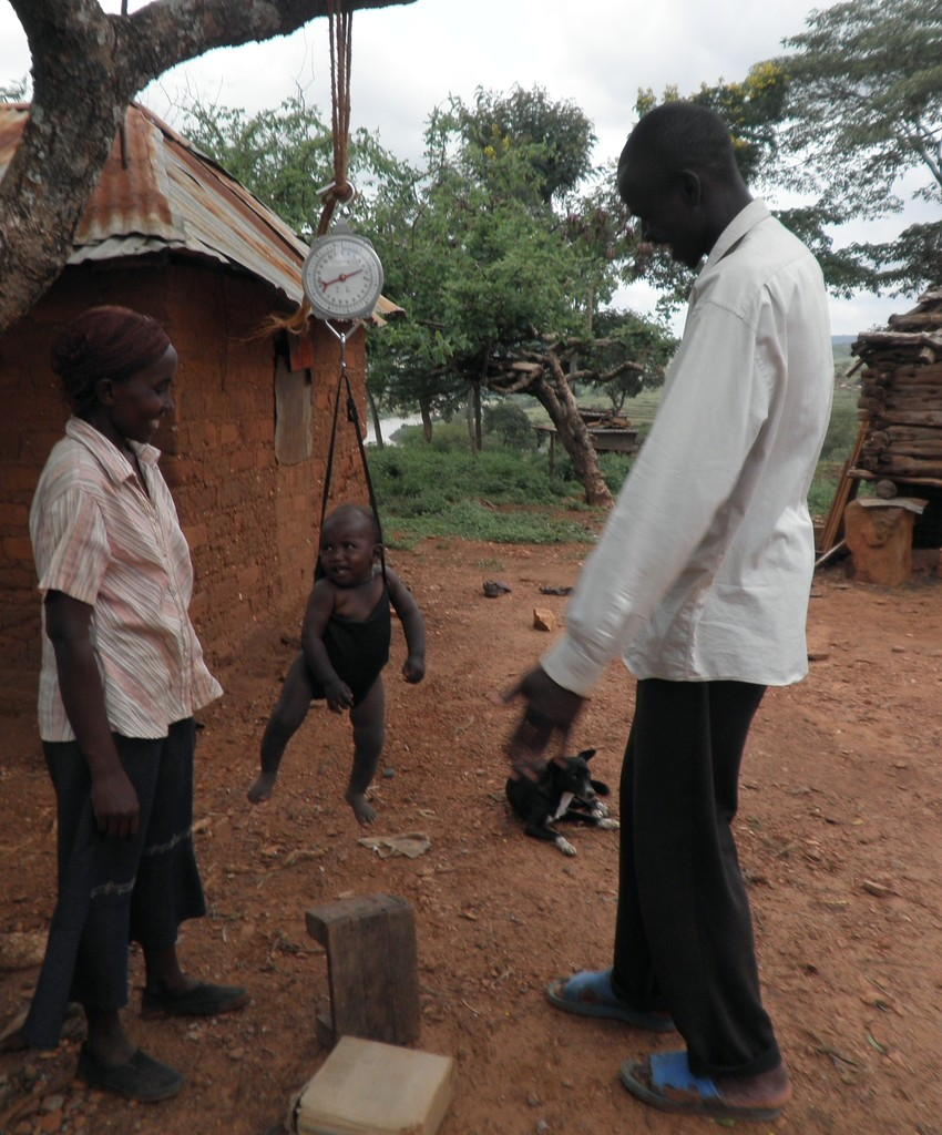 A CHW weighing a child with a hanging Salter scale