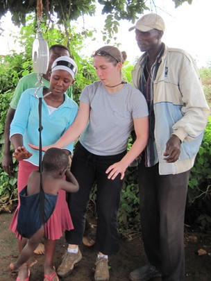 Volunteers weighing a child in the field