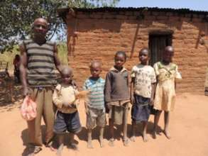 Peter with his children in front of their home