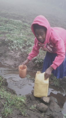 Girl fetching water from existing spring