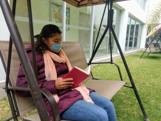 Jacqueline reading a book in our garden