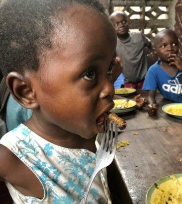 Children eating palm weevil larvae