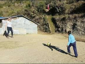 playing football Ms.Paula Nightangale with student