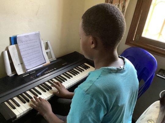 Atim practicing piano at home
