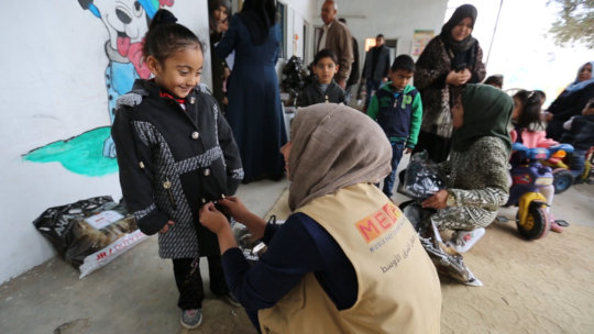 Buttoning up a new coat for a child in Gaza