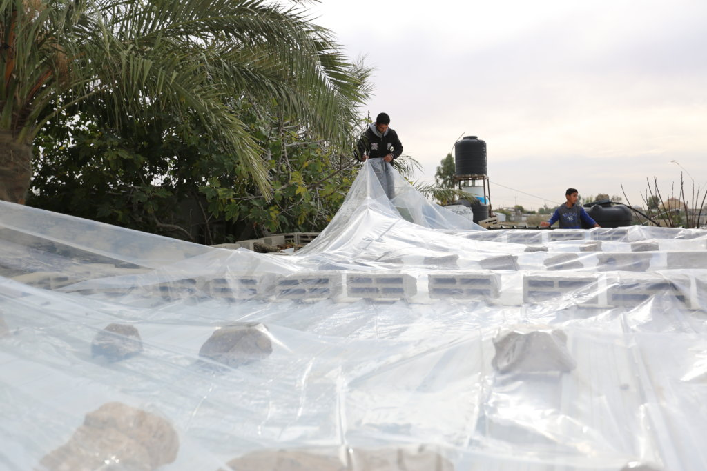 Volunteers cover the roof of a home in Gaza