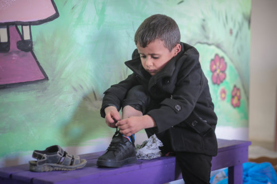 Mohammad putting on his new shoes