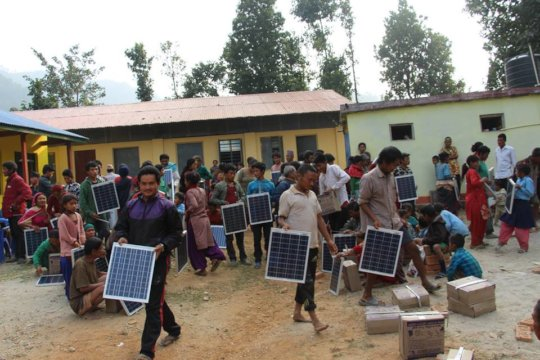 Villagers collect solar sets during distribution