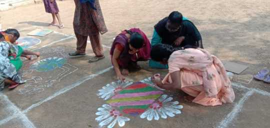 Girls competing in Rangoli, a colorful chalk art