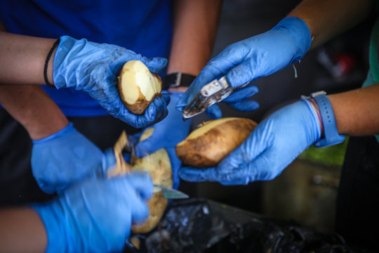 Potato peeling for a hot meal for refugees