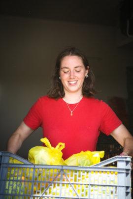 Volunteer with fresh fruit and veg packs