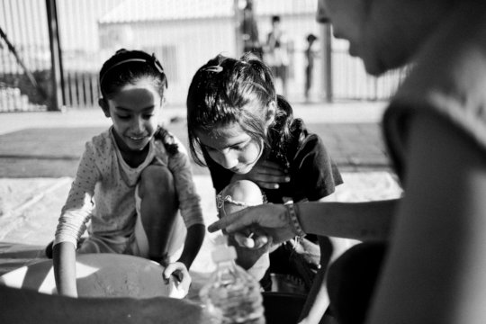 Two girls cooking in Larissa camp in Greece